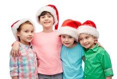 Happy little children in santa hats hugging Royalty Free Stock Image