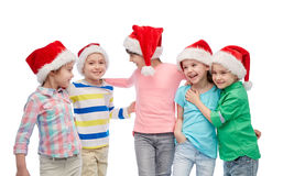 Happy little children in santa hats hugging Royalty Free Stock Photo
