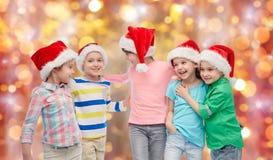 Happy little children in santa hats hugging Royalty Free Stock Photos