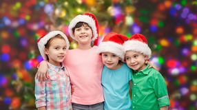 Happy little children in santa hats hugging Royalty Free Stock Photography