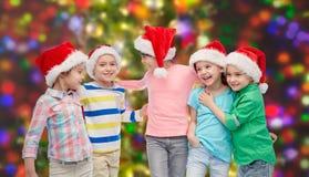 Happy little children in santa hats hugging Stock Image