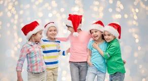 Happy little children in santa hats hugging Stock Photo