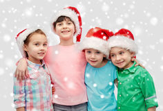 Happy little children in santa hats hugging Royalty Free Stock Images