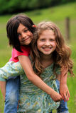 Happy little country girls playing. Two smiling little elementary aged country girls playing piggy-back. Shallow depth of field Stock Images
