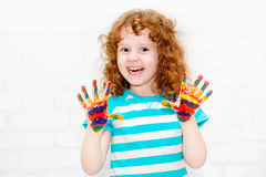 Happy little curly girl. Happy little curly girl with hands in the paint on a light background royalty free stock photography