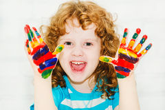 Happy little curly girl with hands in the paint. On a light background royalty free stock image