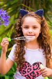 Happy little curly girl playing with soap bubbles on a summer nature, wearing a blue ears of tiger accessories over her Royalty Free Stock Image