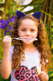 Happy little curly girl playing with soap bubbles on a summer nature, wearing a blue ears of tiger accessories over her Royalty Free Stock Photography