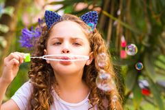 Happy little curly girl playing with soap bubbles on a summer nature, wearing a blue ears of tiger accessories over her Stock Photos