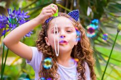 Happy little curly girl playing with soap bubbles on a summer nature, wearing a blue ears of tiger accessories over her Royalty Free Stock Photo