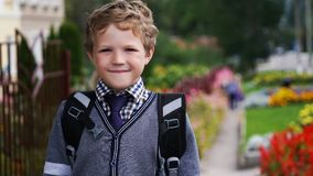 Happy little curly kid boy with backpack or satchel on his first day to school or nursery. Child outdoors on warm sunny stock image