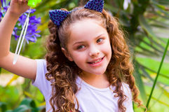 Happy little curly smiling girl playing with soap bubbles on a summer nature, wearing a blue ears of tiger accessories. Over her head in a blurred nature Stock Photography
