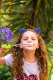 Happy little curly smiling girl playing with soap bubbles on a summer nature, wearing a blue ears of tiger accessories. Over her head in a blurred nature Royalty Free Stock Images