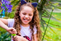 Happy little curly smiling girl playing with soap bubbles on a summer nature, wearing a blue ears of tiger accessories. Over her head in a blurred nature Royalty Free Stock Image