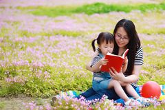 Happy little cute baby girl smile and read book with mother, mom tells story to his daughter in a summer park happy family stock images
