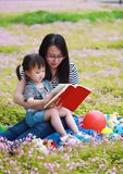 Happy little cute baby girl smile and read book with mother, mom tells story to his daughter in a summer park happy family royalty free stock photo