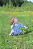Happy little cute baby sits on green grass near forest Royalty Free Stock Photo