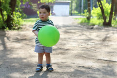 Happy little cute boy holds green balloon and looks away Stock Photos