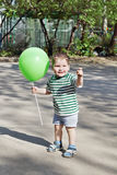 Happy little cute boy holds green balloon and smiles Stock Photo