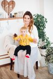 Happy little cute boy sitting together with beautiful mom in stylish decorated studio. stock images