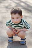 Happy little cute boy squats on asphalt in park at summer day Stock Image