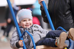 Happy little cute boy swings on playground and his mother hand Stock Photo