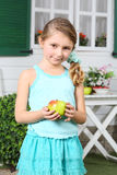 Happy little cute girl in skirt holds apple near white table Stock Photo