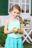 Happy little cute girl in skirt holds apple near white table stock photo