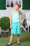 Happy little cute girl in skirt stands near cottage. Stock Photos