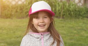 Happy little cute girl in trucker cap smiling and looking at camera while standing in summer garden