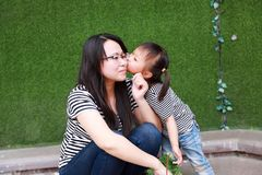Happy little cute lovely baby girl Chinese child kiss and have fun with mother mom at summer park nature happiness childhood. Asian Chinese little cut lovely stock photos