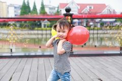 Happy little cute lovely girl Chinese child smile laugh play colorful balloon have fun at summer park nature happiness childhood. Asian Chinese little cut lovely stock images