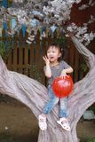 Happy little cute lovely girl Chinese child smile laugh play red balloon have fun at summer park nature happiness childhood. Asian Chinese little cut lovely girl royalty free stock photography