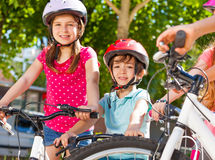 Happy little cyclists having fun at summer park stock image