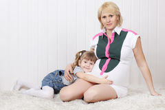 Happy little daughter lies on carpet and hugs belly Royalty Free Stock Photo