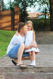 Happy little daughter poses with her father in summer sun royalty free stock images