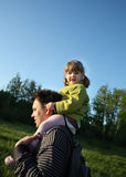 Happy little daughter sits on shoulders of her father Stock Photo