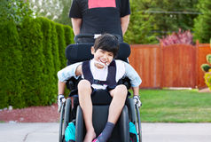 Happy little disabled boy outdoors in wheelchair Royalty Free Stock Photo