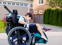 Happy little disabled boy outdoors in wheelchair Royalty Free Stock Photography