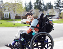 Happy little disabled boy in wheelchair royalty free stock image