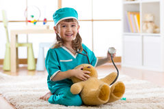 Happy little doctor girl examines teddy bear in nursery room at home Stock Image