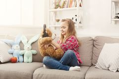 Happy little female child and her teddy bear listening to music on sofa at home Royalty Free Stock Photos