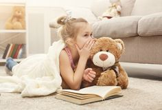 Happy little female child and her teddy bear reading book on the floor at home. Cute happy little casual girl embracing teddy bear, reading book and sharing Royalty Free Stock Images