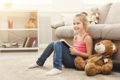 Happy little female child and her teddy bear reading book on the floor at home. Cute happy little casual girl and her teddy bear reading book. Pretty kid at home Stock Photo