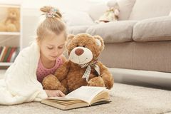 Happy little female child and her teddy bear reading book on the floor at home. Cute happy little casual girl embracing teddy bear and reading book. Pretty kid Stock Photos