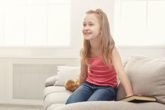 Happy little female child and her teddy bear reading book on sofa at home. Cute happy little casual girl and teddy bear reading book. Pretty kid at home, sitting Royalty Free Stock Images