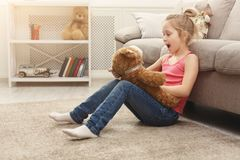 Happy little female child hugging her teddy bear on the floor at home royalty free stock photo