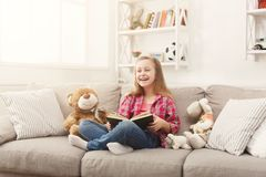 Happy little female child hugging her teddy bear and reading book on sofa at home. Cute happy little casual girl embracing teddy bear and reading book. Pretty Royalty Free Stock Image