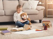Happy little female child hugging her teddy bear and reading. Cute happy little casual girl embracing teddy bear and reading book. Pretty kid at home, sitting on Royalty Free Stock Images