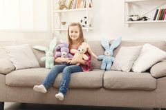 Happy little female child hugging her toy rabbits on sofa at home stock photos